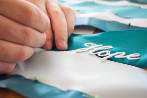 Cal State Fullerton student puts together a ribbon that will be displayed for Ovarian Cancer Awareness Month.