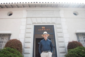 Tom Porter, 67, stands in front of the old Sunkist Fruit Exchange. His family history goes back to a time when the city of Orange, and this building, was a hub for fruit trade. (Photo by Nuran Alteir)
